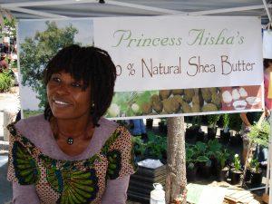 Aisha with banner at market